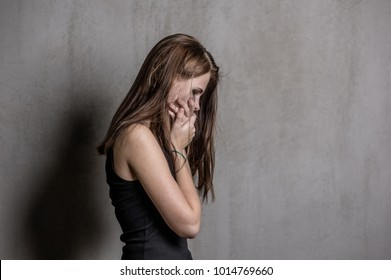 crying teen girl covers her mouth with her hands. Space for text
