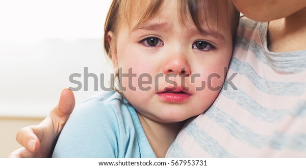 Crying toddler girl being consoled by her mother