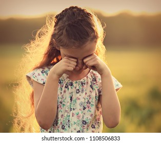 Crying unhappy alone kid girl covering face the hands on summer nature background. Closeup toned  portrait