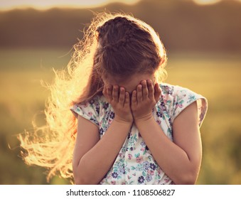 Crying unhappy kid girl covering face the hands on summer nature background. Closeup toned portrait
