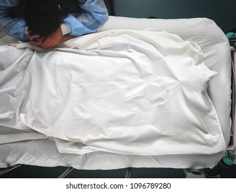 Crying woman hold the hand of dead man, covered with the white bed sheet.