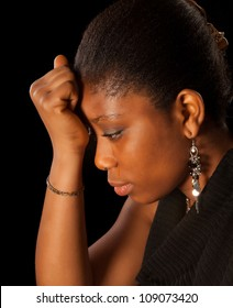 Crying young African Ghanese woman against a black background
