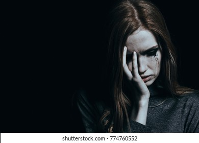 Crying young girl with depression and anxiety. Black background with copy space