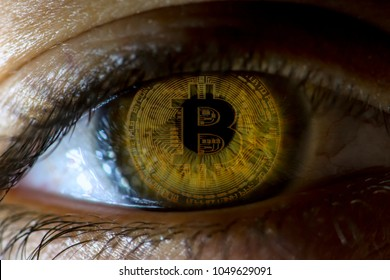 Crypto currency Gold Bitcoin, BTC, Bit Coin. Macro shot of Bitcoin. Eye of a person with the bitcoin coin reflected in the pupil. Blockchain technology, bitcoin mining concept