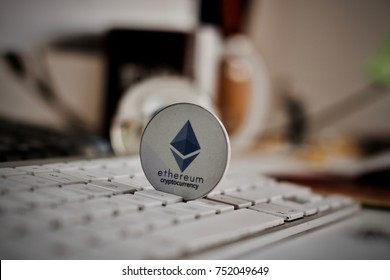 Crypto currency physical grey ethereum token on white keyboard in office.