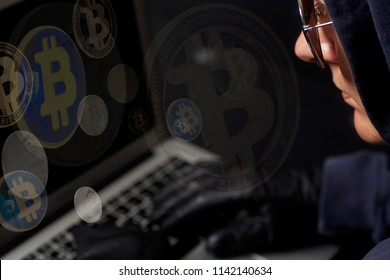 Crypto Hacker with laptop and bitcoin .Concept of internet criminal hacking on black