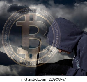 Crypto Hacker with laptop and bitcoin on dramatic sky .Concept of internet criminal hacking