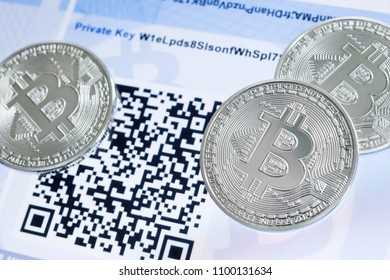Cryptocurrency Bitcoin metallic coins, QR code and paper wallet.