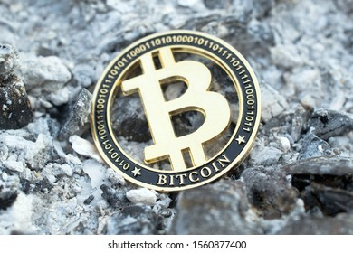 Cryptocurrency, Bitcoin token among ashes. Loss of capital. Close up.