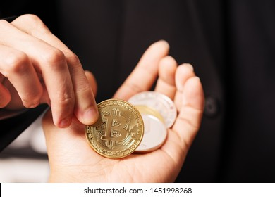 cryptocurrency Bitcoin. Women hold the cryptocurrency coin on hand. Physical bitcoins gold coin