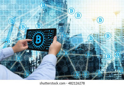 Cryptocurrency, blockchain and bitcoin concept. Distributed ledger technology. Man holding tablet , block chain  icons with smart building background. Blue tone