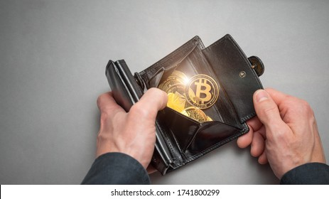 Cryptocurrency coin bitcoin in a black wallet. Bitcoin accumulation, trading sell and buy concept. Cryptocurrency saving symbol.