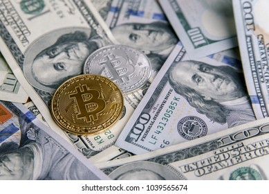 Cryptocurrency coins of golden and silver Bitcoin on banknotes of one hundred dollar. Virtual money investment. Cryptocurrency business concept.
