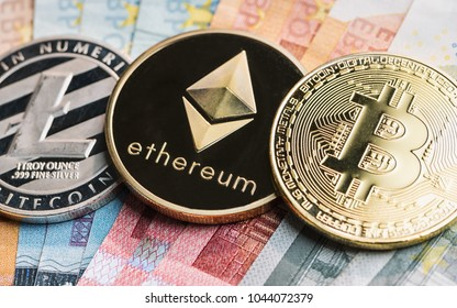 cryptocurrency coins - Litecoin, Bitcoin, Ethereum on top of Euro banknotes
