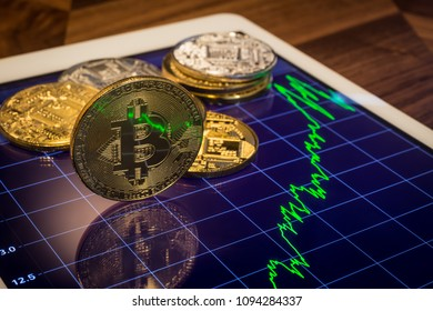 Cryptocurrency concepts, focus Bitcoin on tablet screen that showing light reflect of green price or stock market performance graph. Decentralized transfer exchange digital money through blockchain.