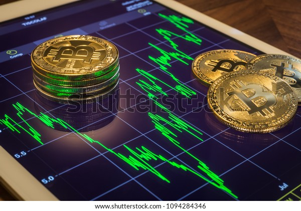 Cryptocurrency concepts, focus Bitcoin on tablet screen that showing green price or stock market performance graph, light reflect. Decentralized, transfer or exchange digital money through blockchain.