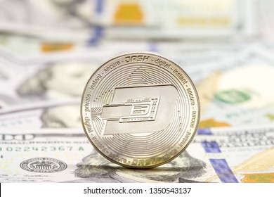 Cryptocurrency dash coin displayed on a heap of one hundred dollar bills.