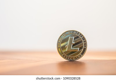 Cryptocurrency electronic money sign, focus on metal Litecoins stack on wooden table, blur white background copy space. Concept of decentralized, transfer or exchange digital money through blockchain.