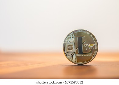 Cryptocurrency electronic money sign, focus on metal Litecoin stack on wooden table, blur white background copy space. Concept of decentralized, transfer or exchange digital money through blockchain.