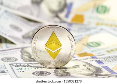 Cryptocurrency ethereum coin displayed on a heap of one hundred dollar bills.