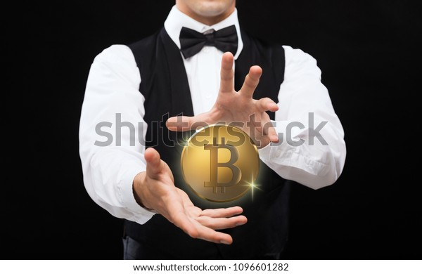 cryptocurrency, financial technology and business concept - close up of magician with bitcoin making trick over black background