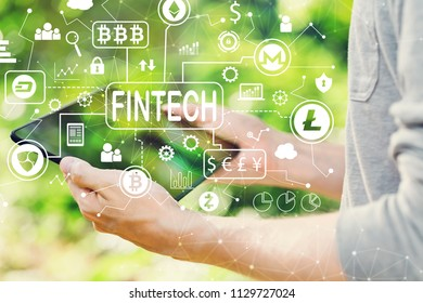 Cryptocurrency fintech theme concept with man holding his tablet computer outside in the park