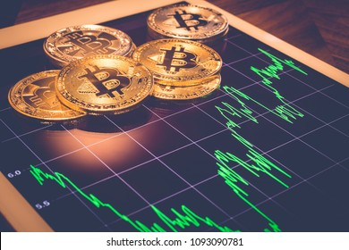 Cryptocurrency, focus Bitcoin on tablet screen that showing green price or stock market performance graph, light reflect with vintage filter. Decentralized, exchange digital money through blockchain.