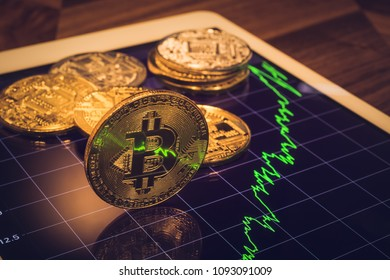 Cryptocurrency, focus Bitcoin on tablet screen that showing light reflect of green price or stock market performance graph, dark tone. Decentralized transfer exchange digital money through blockchain.