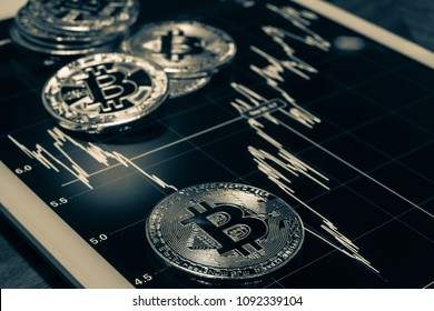 Cryptocurrency, focus Bitcoin sign on tablet screen that showing price or stock market performance graph, dark tone black and white filter. Decentralized, transfer digital money through blockchain.