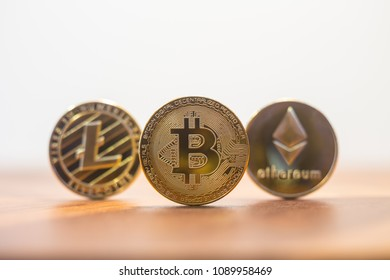 Cryptocurrency focus on Bitcoin, blury Litecoin and Ethereum, on wooden table with white wall background copy space. Concept of decentralized, transfer or exchange digital money through blockchain.
