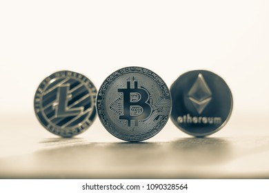 Cryptocurrency focus on Bitcoin, blury Litecoins and Ethereum, on wooden table with background copy space, black and white filter. Concepts of transfer or exchange digital money through blockchain.