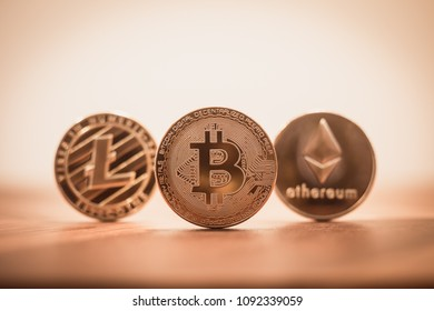 Cryptocurrency focus on Bitcoin, blury Litecoins and Ethereum, on wooden table with background copy space, retro vintage filter. Concepts of transfer or exchange digital money through blockchain.