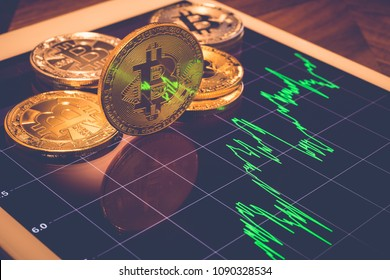 Cryptocurrency gold metal, focus bitcoin sign on tablet screen that showing light reflex of green price or stock market performance graph, vintage filter. Concept of exchange money through blockchain.