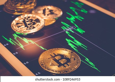 Cryptocurrency gold metal, focus on bitcoin sign, coins put on tablet screen that showing green price or stock market performance graph, vintage filter. Concept of exchange money through blockchain.