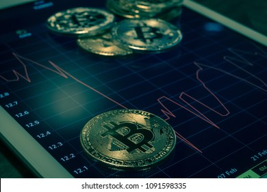 Cryptocurrency gold silver metal, focus on bitcoin sign, coins put on modern tablet screen that showing red price or stock market drop graph, dark tone. Concept of exchange money through blockchain.