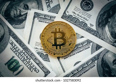 Cryptocurrency golden bitcoin coin above American dollar banknotes. Conceptual image for crypto currency, toned