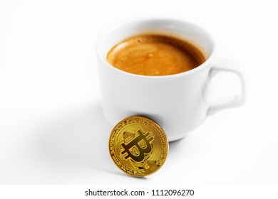 Cryptocurrency golden bitcoin standing on coffee cup isolated on a white background