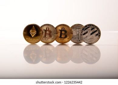 Cryptocurrency including Ethereum Bit coins and Lite coin standing on their rims on a reflective white surface with room for text and copy space.