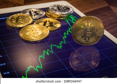 Cryptocurrency metal, focus on gold bitcoin, coins put on tablet screen that showing green price or stock market performance graph,  Concept of transfer or exchange digital money through blockchain.