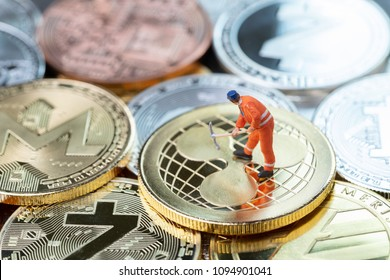 Cryptocurrency mining concept, miniature worker minor standing on various golden physical digital money Ripple, xrp.