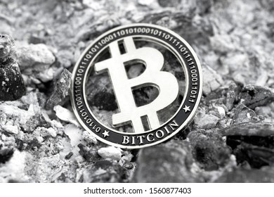 Cryptocurrency, monochrome Bitcoin token among ashes. Loss of capital. Black, White, Close up.