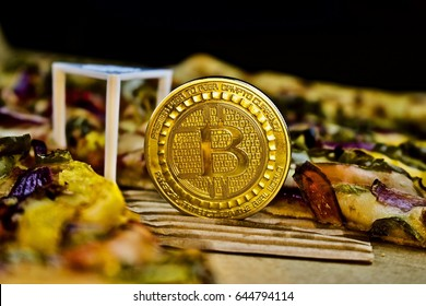 Cryptocurrency physical gold bitcoin coin near the pizza