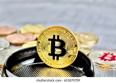 Cryptocurrency physical gold bitcoin coin on black ring.