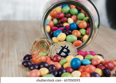 Cryptocurrency physical gold bitcoin coin and gold peercoin coin near colorful sweets