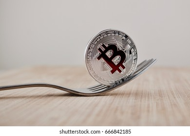 Cryptocurrency physical silver bitcoin coin with red sign on the wooden board.
