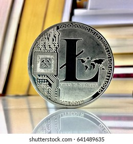 Cryptocurrency silver litecoin coin near books