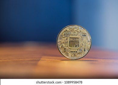 Cryptocurrency symbol electronic sign, focus on gold metal Bitcoin stack on wooden table, blur dark blue wall background copy space. Concept of transfer or exchange digital money through blockchain.