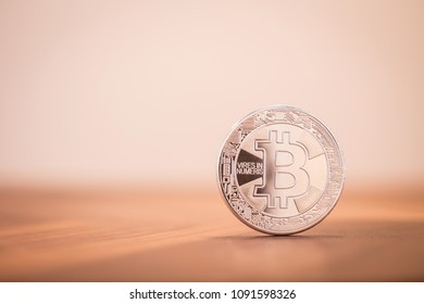 Cryptocurrency symbol electronic sign, focus on silver metal Bitcoin stack on wooden table, blur white background copy space. Decentralized concept, transfer exchange digital money through blockchain.