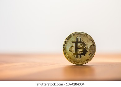 Cryptocurrency symbol electronic sign, focus on gold metal Bitcoin stack on wooden table, blur white background copy space. Decentralized, transfer or exchange digital money through blockchain.