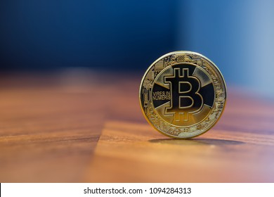 Cryptocurrency symbol sign, focus on gold metal Bitcoin stack on wooden table, blur dark blue wall background copy space. Decentralized, transfer or exchange digital money through blockchain.